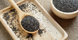 Chia seed on a wooden spoon against burlap background