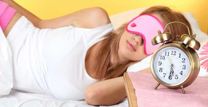 young beautiful woman sleeping on bed with eye mask and  alarm c